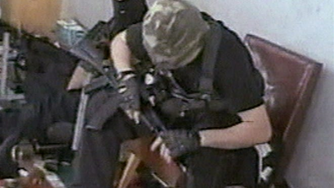 Hostages sit with their weapons in the school in Beslan, Russia, taken during the early part of the siege which began on  Sept. 1, 2004, and ended with over 300 people dead.