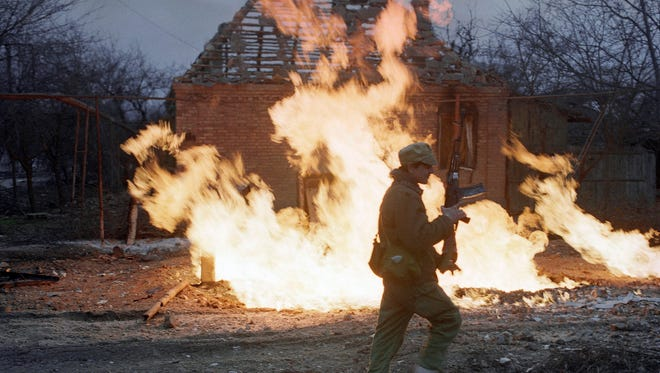 In this 1995 photo, a Chechen rebel fighter runs past a burning building in the center of Grozny, Chechnya, Russia. Two suspects in the Boston Marathon bombing have been identified to The Associated Press as coming from a Russian region near Chechnya. In the past, insurgents from Chechnya and neighboring restive provinces in the Caucasus have been involved in terror attacks in Moscow and other places in Russia.
