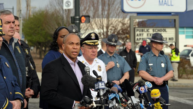 Massachusetts Gov. Deval Patrick, at microphone, updates the public on the Boston manhunt with local and state police officials.