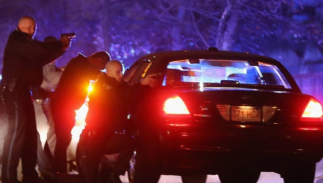 Police with guns drawn conduct a massive police operation in Watertown, Mass.