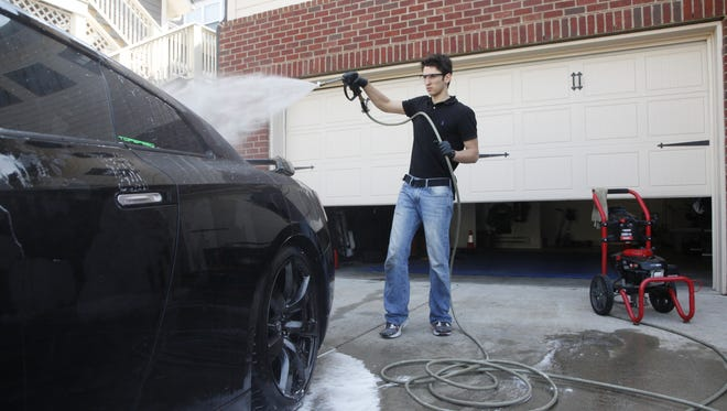 Christopher Dalton uses a pressure washer while detailing a Nissan GTR at his garage. Dalton dropped out of college in order to build his car washing business he started in high school into a performance quality detailing business.