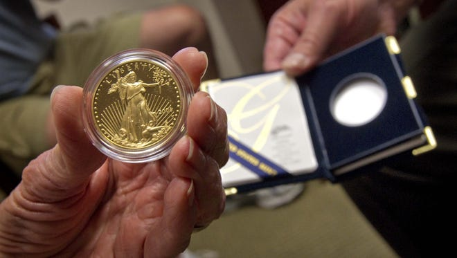 A gold buyer inspects a 1-ounce gold coin at the Republic Monetary Exchange in Phoenix.