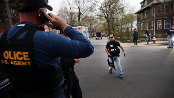 Police converge near the scene where  bombing suspect Dzhokhar Tsarnaev was in hiding on Friday in Watertown, Mass.