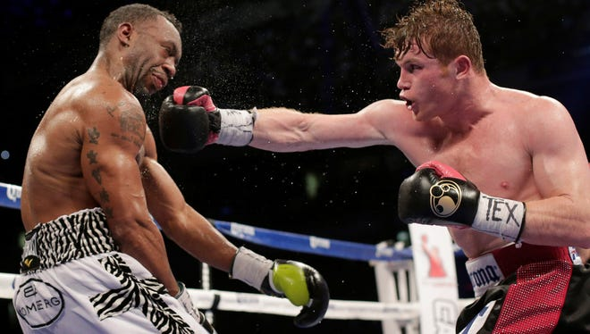 """Saul """"Canelo"""" Alvarez, right, lands a punch on Austin Trout during during the ninth round of their 154-pound title unification bout Saturday in San Antonio."""