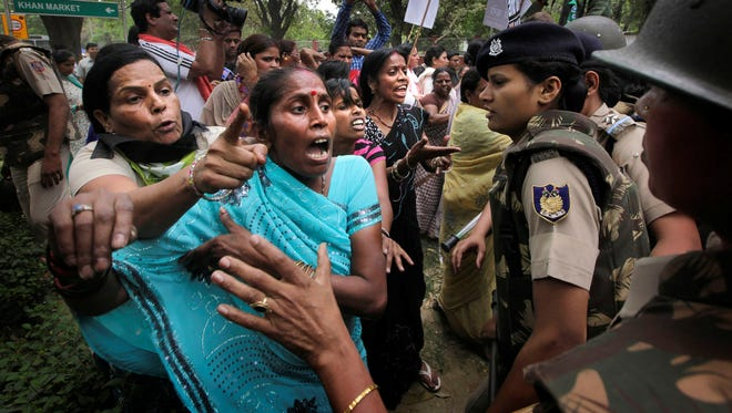 Indian activists of India's main opposition Bharatiya Janata Party jostle with Indian police outside ruling United Progressive Alliance chairperson Sonia Gandhi's residence during a protest against the rape of a 5-year-old girl in New Delhi, India, Sunday, April 21, 2013.