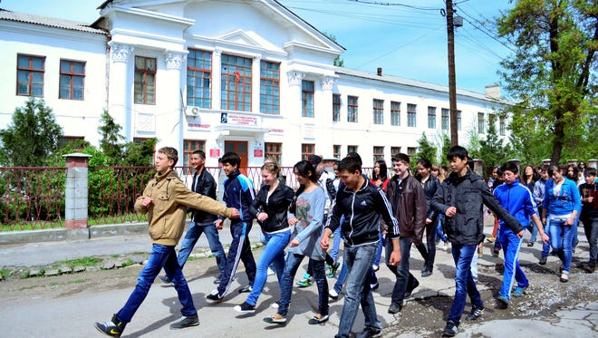 Students march in front of a school where Tamerlan Tsarnaev studied in a small Kyrgyz city, Tokmok, east of the country's capital of Bishkek.