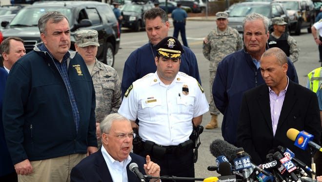 Watertown Police Chief Ed Deveau, back right, listens as Boston Mayor Thomas Menino (not pictured) speaks during a news conference Friday regarding the suspects in the Boston bombing case.