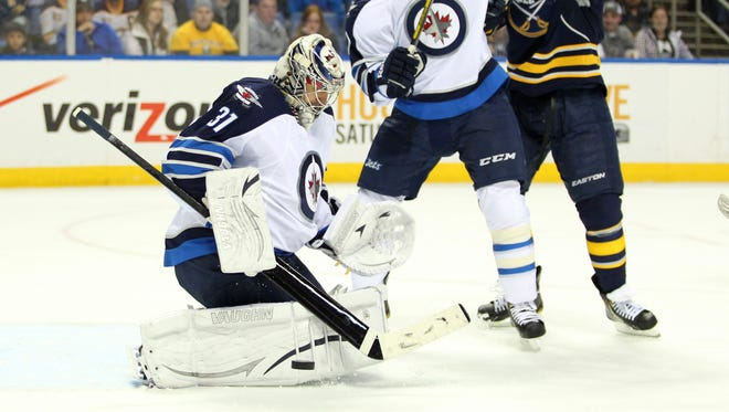 Ondrej Pavelec makes one of his 24 saves for the Jets.