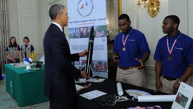 President Obama holds a model rocket during the White House Science Fair.