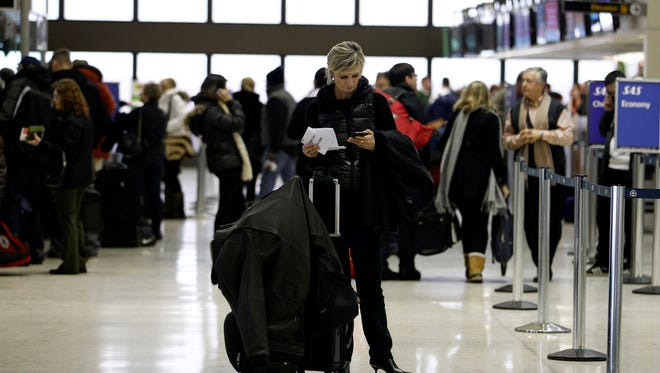 A traveler checks her phone near the ticketing area at Newark Liberty International Airport. Some mobile sites are better than others, and some don't live up to the possibilities of the airline app.