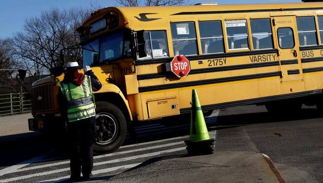 A crossing guard waves as a bus passes in New York.