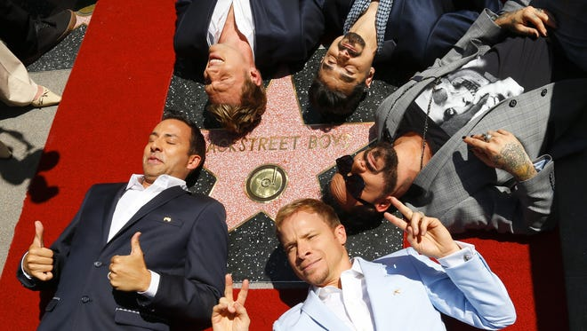 Singers Howie Dorough (clockwise from left), Nick Carter, Kevin Richardson, AJ McLean and Brian Littrell of the Backstreet Boys take their star on the Hollywood Walk of Fame lying down on April 22.