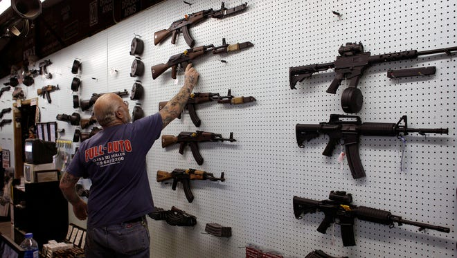 Gun dealer Mel Bernstein takes down an AK-47 assault rifle from a sales rack in February at his shooting range and gun store, Dragonman's, east of Colorado Springs, Colo.
