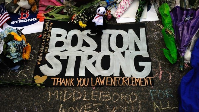 A sign with the names of the Boston Marathon bombing victims is placed at a makeshift memorial near the site of the blasts on Sunday in Boston.