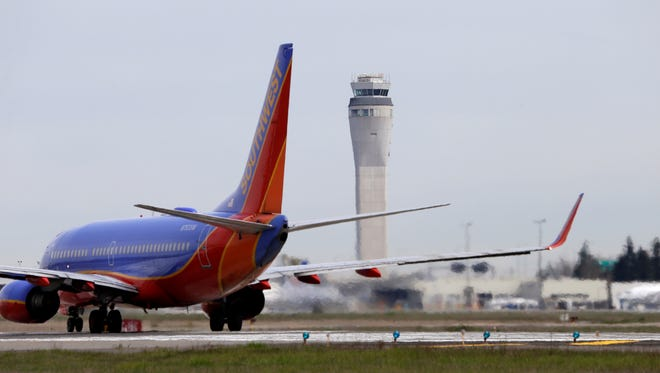 A Southwest airlines jet waits to depart in view of the air traffic control tower at Seattle-Tacoma International Airport on Tuesday.