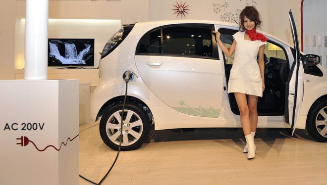 A model poses next to Mitsubishi's i-MiEV model, the world's first volume production electric vehicle, at the Tokyo Motor Show in Chiba on October 21, 2009.