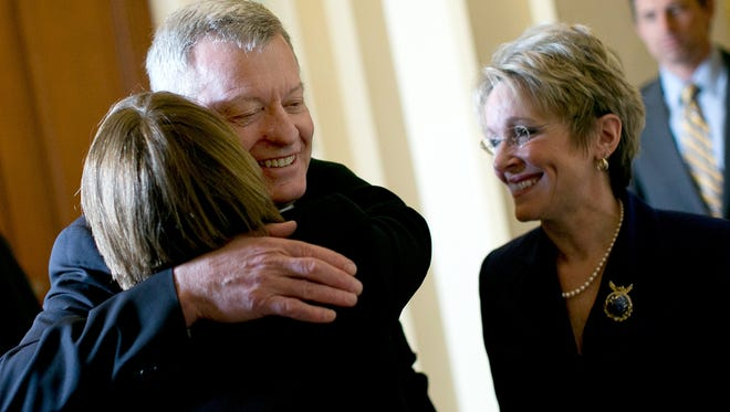 Sen. Max Baucus, D-Mont., is hugged by Sen. Amy Klobuchar, D-Minn., while walking with his wife, Melodee Hanes, at the Capitol on Wednesday.