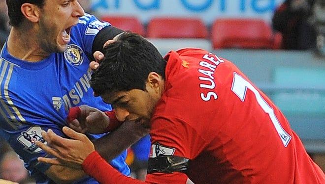 Luis Suarez clashes with Chelsea's Branislav Ivanovic.