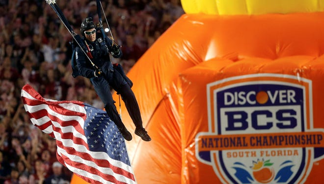 Amember of the U.S. Army jumps into the stadium before the first half of the BCS National Championship between Alabama and Notre Dame in Miami. The conference commissioners in charge of putting together the four-team playoff system that will start after the 2014 regular season are meeting this week to determine details of the new College Football Playoff.