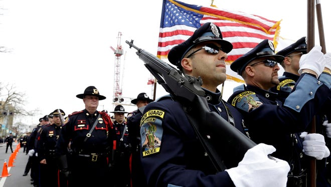 A police honor guard lead law enforcement officials to a memorial service April 24 for fallen MIT police officer Sean Collier, in Cambridge, Mass.