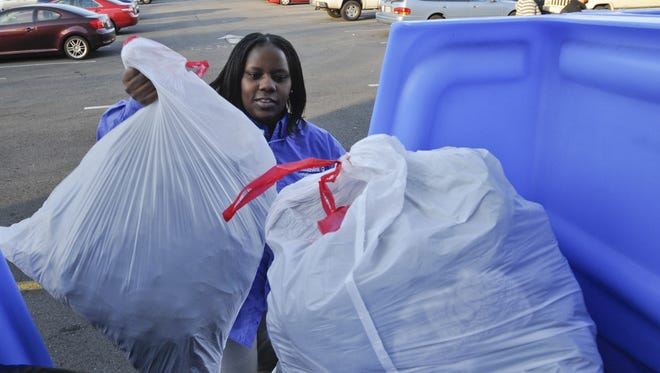 Goodwill employee, Natasha Wiggins, carries clothes donations to a bin outside of the store in West Falls Church, Va. on Friday Dec. 28, 2012.  Goodwill has seen donation boxes from a number of for-profit clothing recyclers pop up across the country, confusing consumers about which bins are for charity and which aren't.