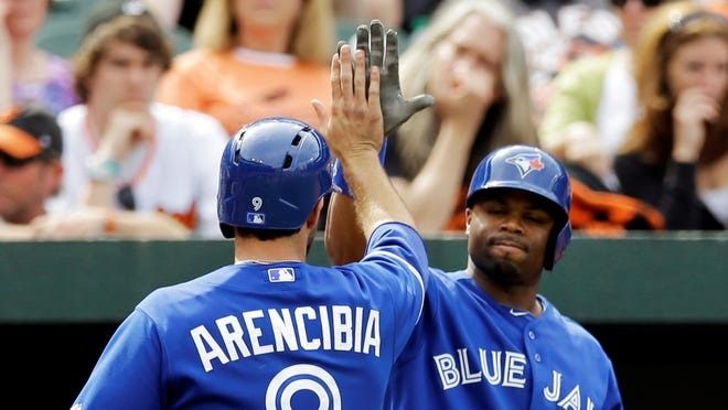 Blue Jays' J.P. Arencibia, left, high-fives Rajai Davis after scoring a run on a bases-loaded walk in the 11th inning.