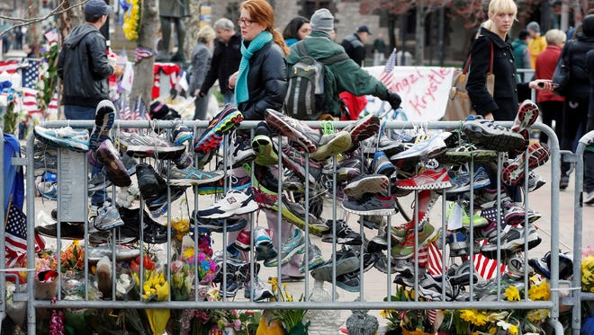 Running shoes hang from a barrier at a makeshift memorial in Copley Square in Boston, Wednesday, April 24, 2013. Businesses opened and traffic was allowed to flow all the way down Boylston Street on Wednesday morning for the first time since two explosions at the Boston Marathon on April 15.