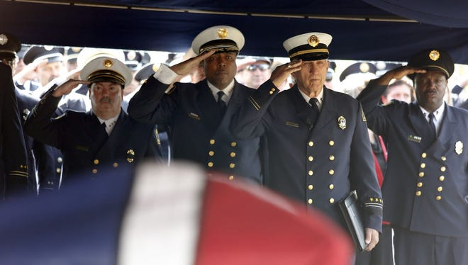 """Dallas Fire-Rescue Chief Louie Bright III, center left, and retired Dallas Fire Department chaplain Denny Burris, center right, salute the casket of Dallas Fire-Rescue Capt. Kenneth """"Luckey"""" Harris Jr. Harris was killed in the West Fertilizer Co. plant explosion on April 17."""