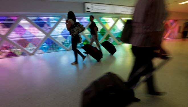 Passengers travel through an airport in Miami on Sept. 27, 2012. A new survey shows that Americans aren't taking vacations as often as they need them.