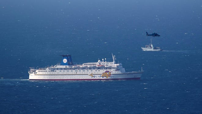 An Israeli military ship and an Israeli air force helicopter operate next to a cruise ship off the coast of Haifa, northern Israel, on April 25.