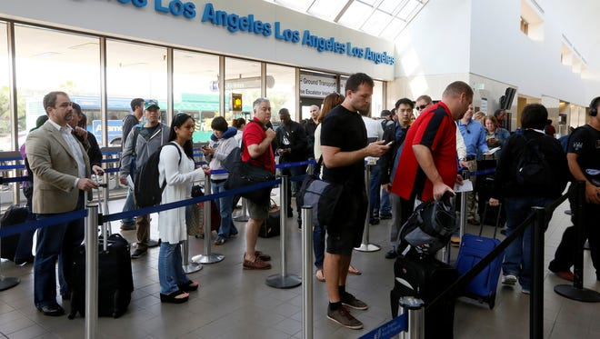 Travelers wait in line Monday at Los Angeles International Airport.