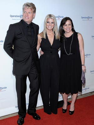 """Singer Jessica Simpson, center, her father Joe Simpson, right, and mother Tina Simpson arrive at the Operation Smile """"Smile Gala"""" in Beverly Hills, Calif., on Oct. 2, 2009."""