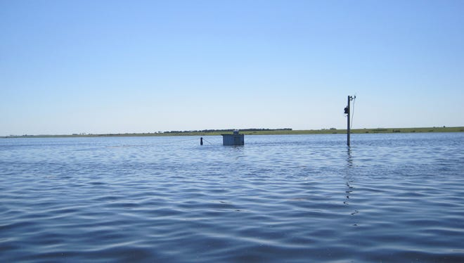 The Souris River peaks near Westhope, N.D., during the great Souris River flood of July 2011. USGS equipment is stored in cooler bolted to roof of gagehouse because water level was above gagehouse shelf.