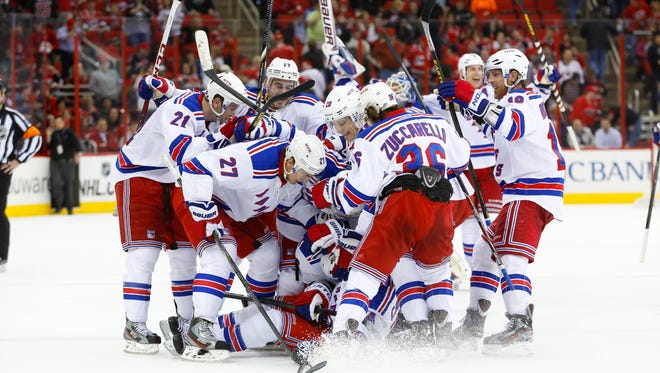 New York Rangers right wing Ryan Callahan celebrates his overtime game winning goal with teammates against the Carolina Hurricanes. The Rangers defeated the Hurricanes 4-3 to clinch a playoff berth.