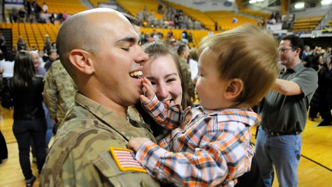 Pvt. Thomas Davies is greeted by son Zackary, 9 months, and wife Tiffany at a homecoming in Kalamazoo, Mich., after a 10-month tour in Afghanistan.