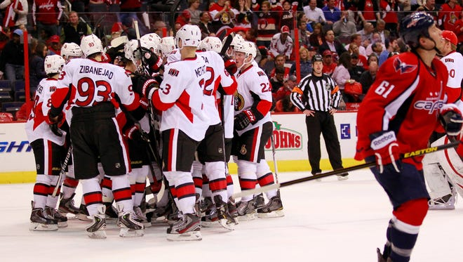 Ottawa Senators defenseman Sergei Gonchar (55) is mobbed by teammates after scoring the game-winning goal against the Washington Capitals in overtime at Verizon Center.