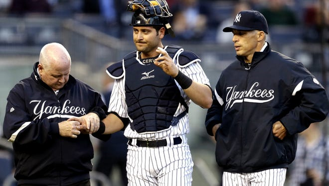Yankees trainer Steve Donohue, left, checks on catcher Francisco Cervelli, center, as manager Joe Girardi looks on. Cervelli left the game in the first inning. He broke his right hand and will miss at least six weeks.
