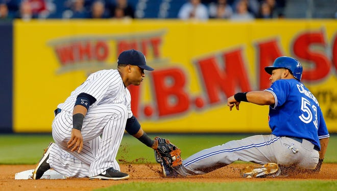 Robinson Cano tags out Melky Cabrera as he tries to steal second base in the second inning. The Yankees topped the Blue Jays, 6-4.