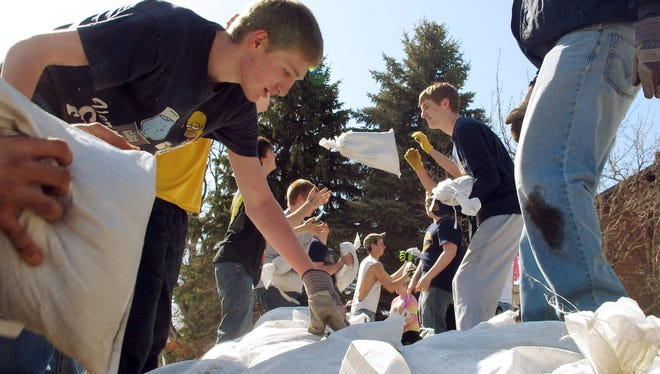 High school students toss sandbags down a line along the Red River on Friday in Fargo, N.D. Hundreds of students pitched in to place 100,000 sandbags around Fargo and help protect homes against Red River flooding.
