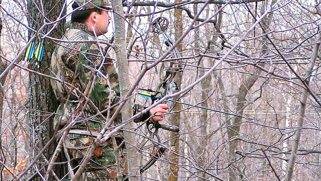Brian Castellano of Deer River, Minn., waits with his bow during a deer hunt in fall 2004. Some states with Sunday hunting blue laws may bend just enough to allow bow hunting on Sundays.