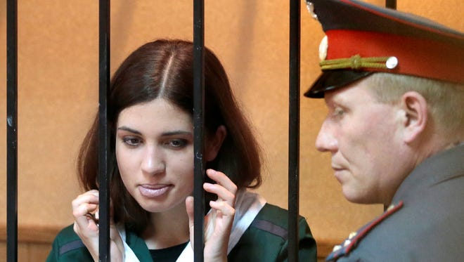 Nadezhda Tolokonnikova, a member of the feminist punk band, Pussy Riot, listens from behind bars at a district court in Russia's province of Mordovia, Friday, where he is serving a sentence for hooliganism. The court rejected her bid for parole of her two-year sentence.