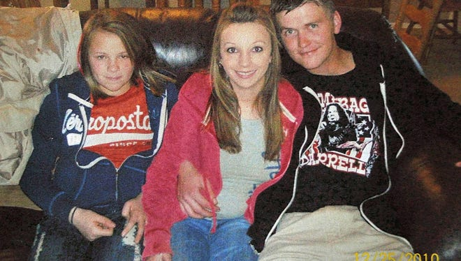 This Dec. 25, 2010, file photo provided by Clint Dunn shows his 13-year-old daughter, Hailey Dunn, left, posing for a photo with her mother, Billie Jean Dunn, center, and her mother's boyfriend, Shawn Adkins, in Colorado City, Texas.