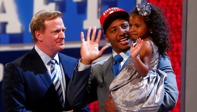 Eric Reid (LSU) holds daughter LeiLani Reid as he is introduced by NFL commissioner Roger Goodell as the number eighteen  overall pick to the San Francisco 49ers during the 2013 NFL Draft at Radio City Music Hall.