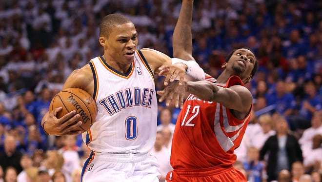 Russell Westbrook (0) of the Oklahoma City Thunder is called for an offensive foul as he drives the ball against Patrick Beverley (12) of the Houston Rockets.