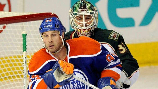 Edmonton Oilers' Ryan Smyth, left, screens Minnesota Wild's goalie Niklas Backstrom during an April 16 game.