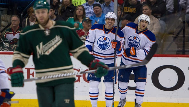 Edmonton Oilers forward Taylor Hall (4) smiles with forward Taylor Yakupov (64) after a goal during the second period against the Minnesota Wild at Xcel Energy Center.