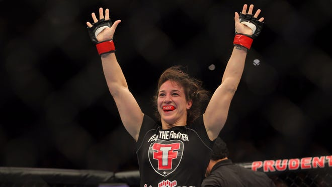 Apr 27, 2013; Newark, NJ, USA; Sara McMann (black shorts)  celebrates defeating Sheila Gaff (not pictured) during UFC 159 at the Prudential Center. Mandatory Credit: Brad Penner-USA TODAY Sports ORG XMIT: USATSI-131484 ORIG FILE ID:  20130427_hcs_ae5_062.JPG