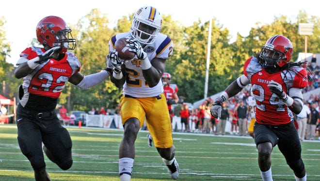 In this photo taken Sept. 22, 2012 and provided by Tennessee Tech University,  Tech wide receiver Da'Rick Rogers (21) scores a touchdown between Southeast Missouri State defenders Josh Coleman (32) and Kweku Arkorful (24) during a college football game in Cape Girardeau, Mo.