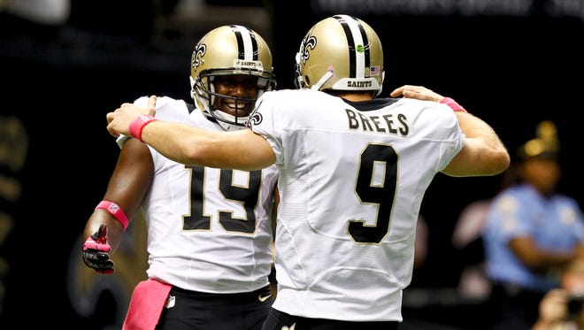 New Orleans Saints quarterback Drew Brees (9) celebrates with wide receiver Devery Henderson (19) to break the NFL record for consecutive games throwing a touchdown at 48 games eclipsing a record once held by Johnny Unitas during the first quarter of a game against the San Diego Chargers at the Mercedes-Benz Superdome.