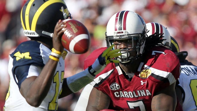 South Carolina Gamecocks defensive end Jadeveon Clowney (7) rushes as Michigan Wolverines quarterback Devin Gardner (12) throws the ball during the second half of the 2013 Outback Bowl at Raymond James Stadium.